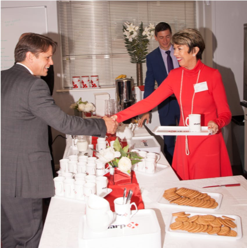 Jean Freeman shaking hands with a man in a grey suit over a long table filled with teacups and biscuits