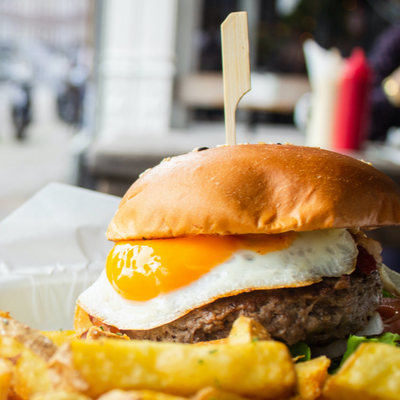 street food plate of crispy golden chips and a beef burger with a fried egg and a golden crisp bun