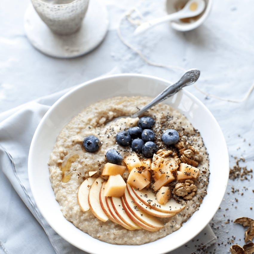 a white bowl filled with creamy porridge topped with stewed apples, blueberries nuts and seeds