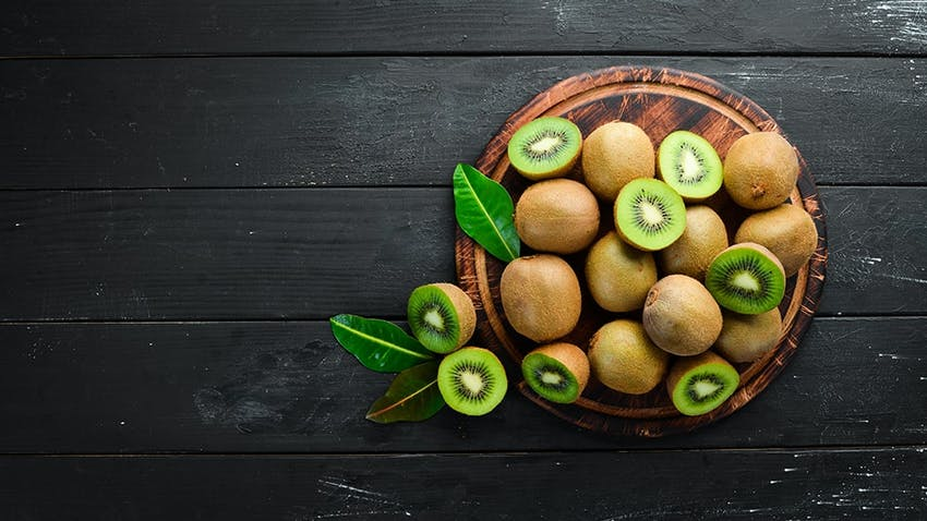 birds eye view of a wooden chopping board topped with whole and halved fresh kiwis