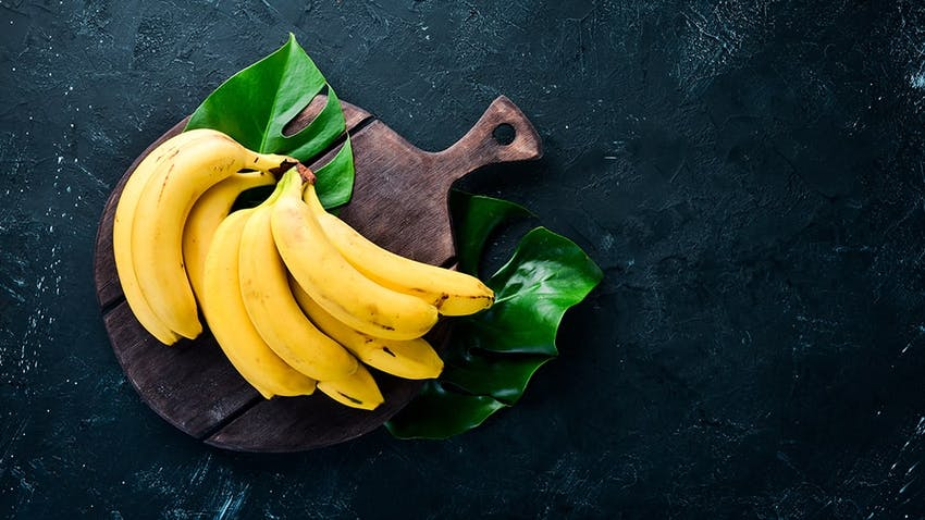 a bunch of yellow bananas on a wooden circular chopping board placed on banana leaf