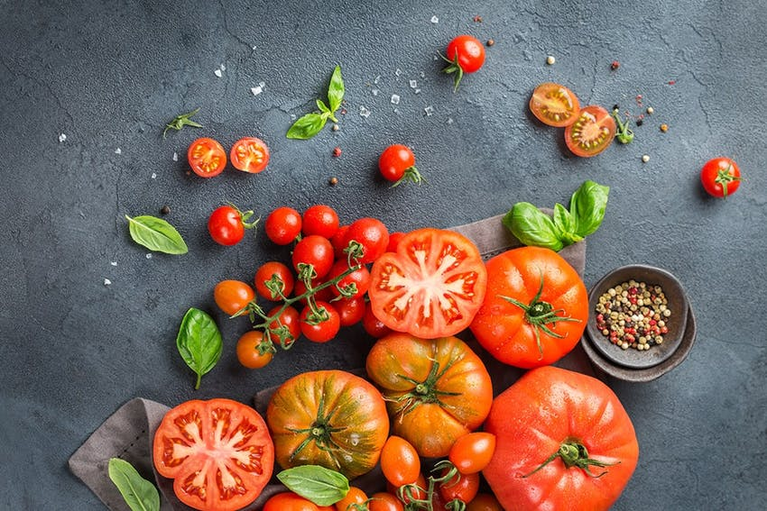 birds eye view of cherry vine and beefsteak tomatoes scattered across a grey marble tabletop and a pot of tomato seeds
