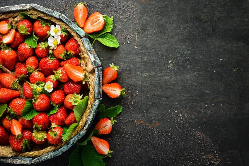 a punnet filled with red strawberries halved strawberries and mint leaves
