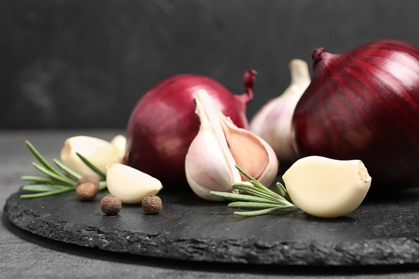 red onions garlic bulbs and garlic cloves with peppercorns and rosemary on a dark stone slate