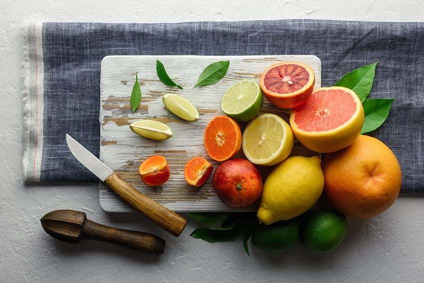 light wooden chopping board on top of a table runner topped with whole and halved limes, lemons and orange citrus fruits