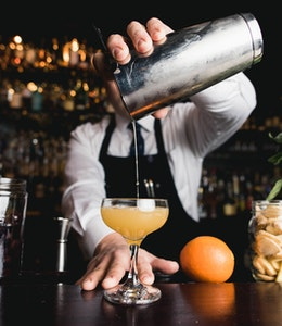 bartender holds a cocktail shaker over a half serve glass pouring in an alcoholic drink