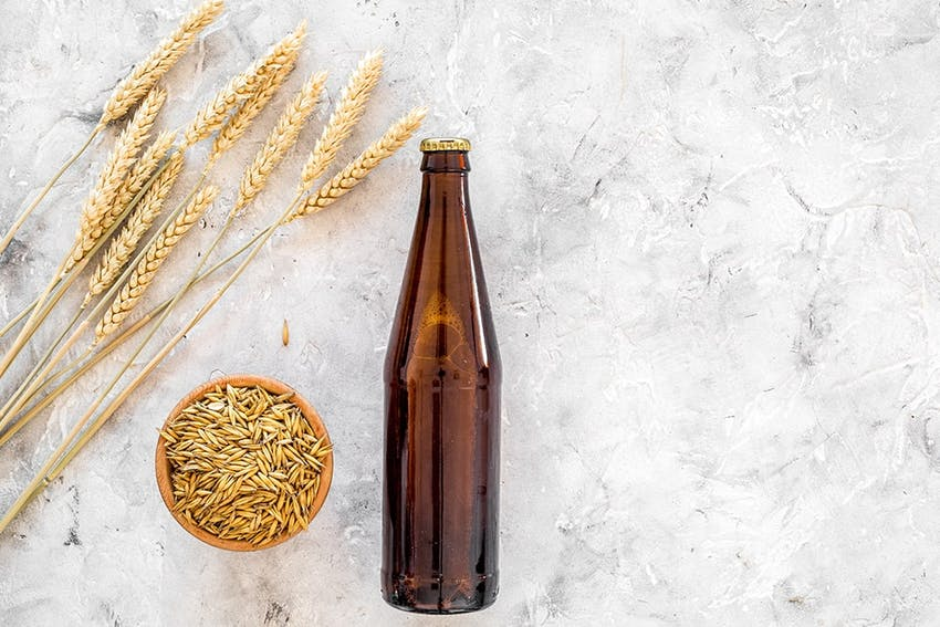 a bottle of beer on a white marble worktop next to a bowl of wheat grains and stalks of wheat