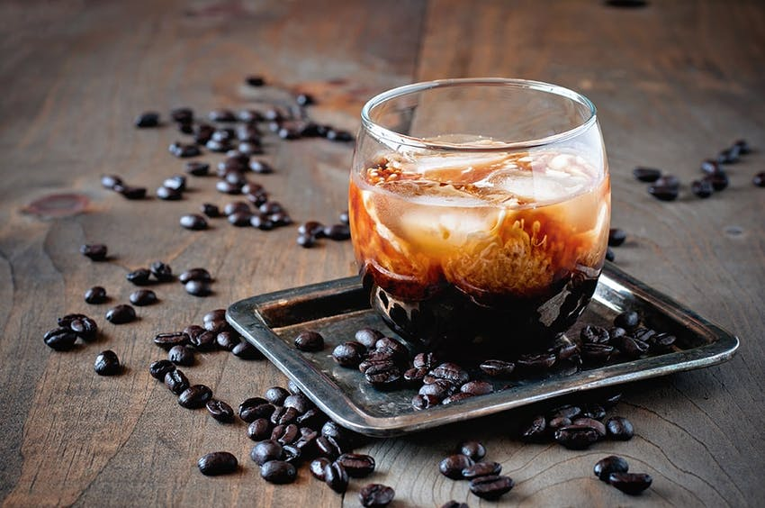 a small glass filled with kahlua on a metal tray surrounded by scattered coffee beans