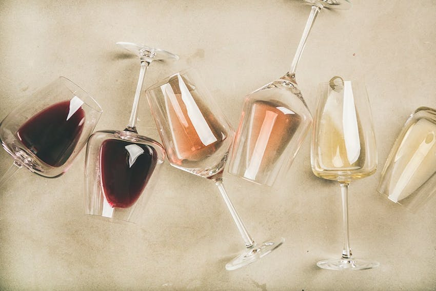 six wine glasses containing red white and rose creatively lined up in different angles on a white tablecloth