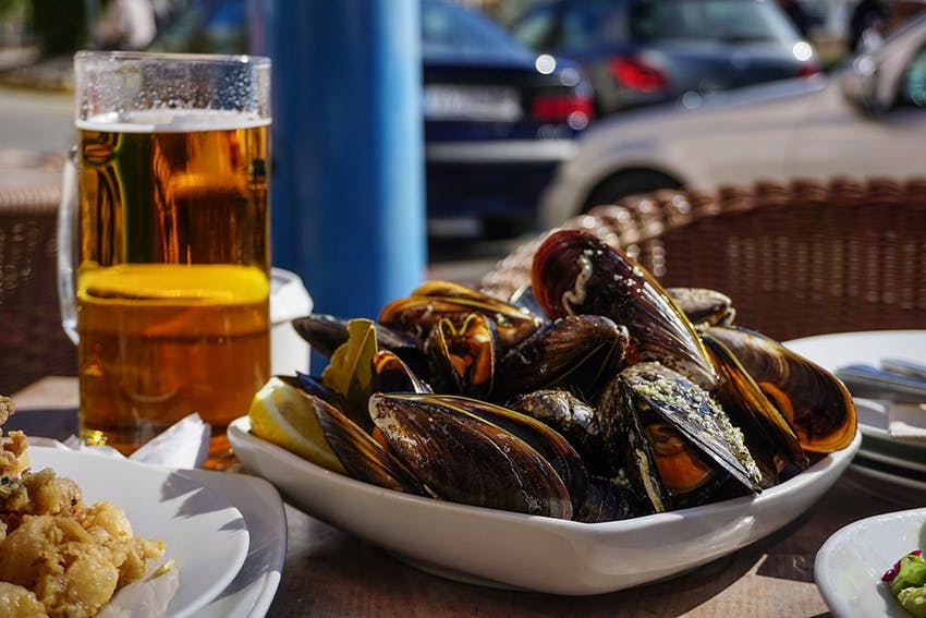 a bowl of oysters next to a pint glass of beer on an outdoor dining table