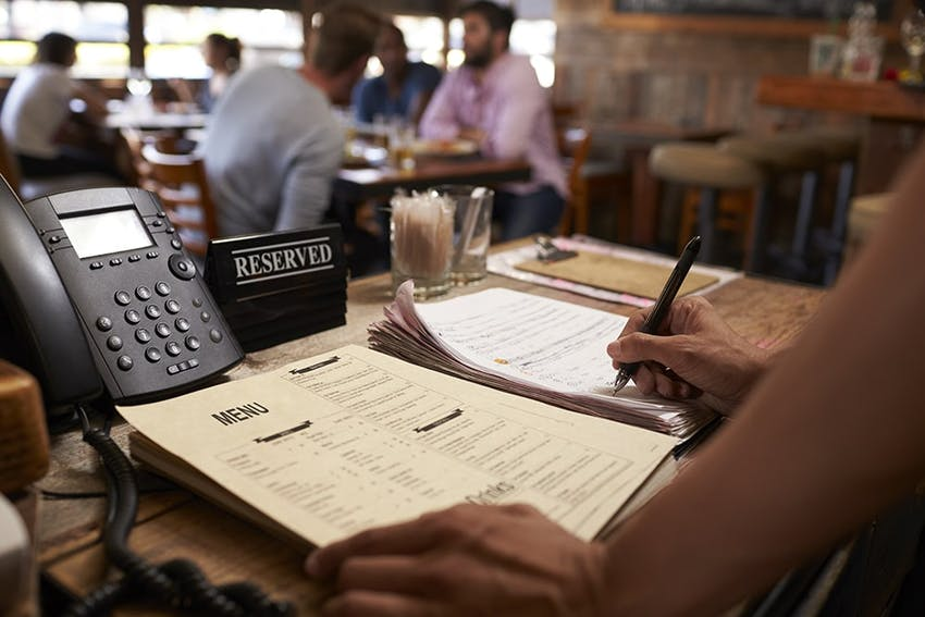 restaurant desk with phone reserved signs and woman leant over a list of menus writing down allergen information