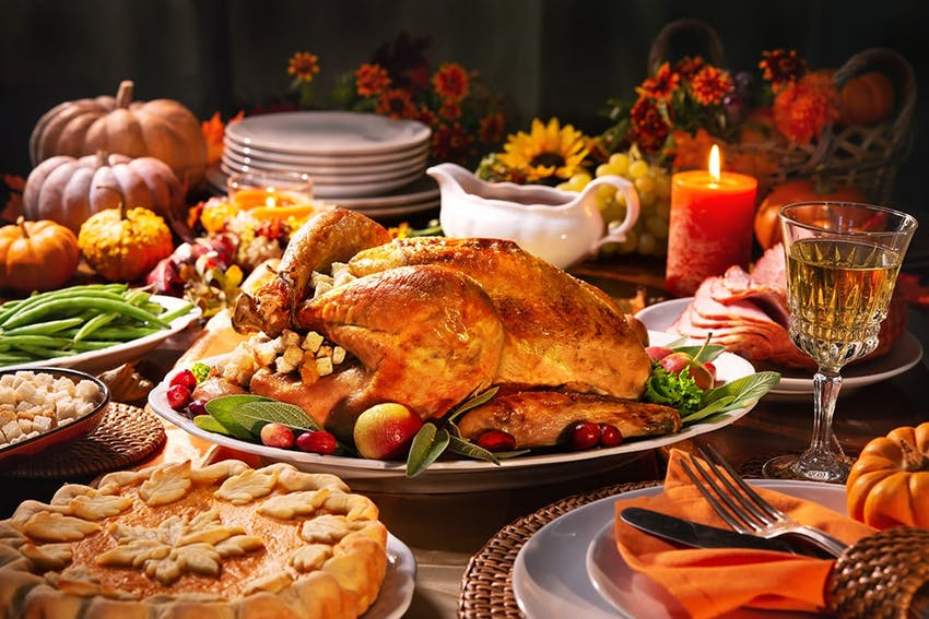 christmas dinner with a turkey centrepiece, festive pie, green beans, gravy, honey roast ham and decorative flowers