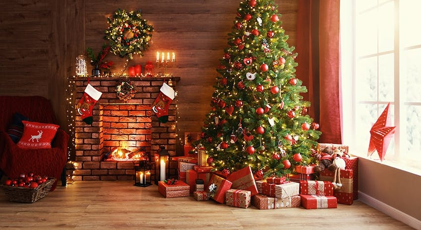 green christmas tree surrounded by wrapped presents next to a warming fireplace and a cosy armchair