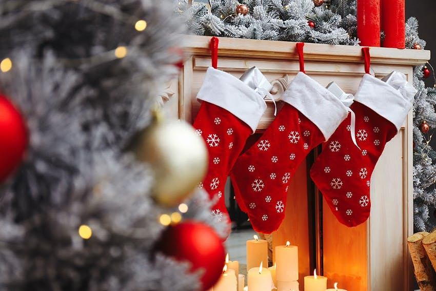 three red christmas stockings hung on the fireplace above candles next to a frosted christmas tree with red and gold baubles
