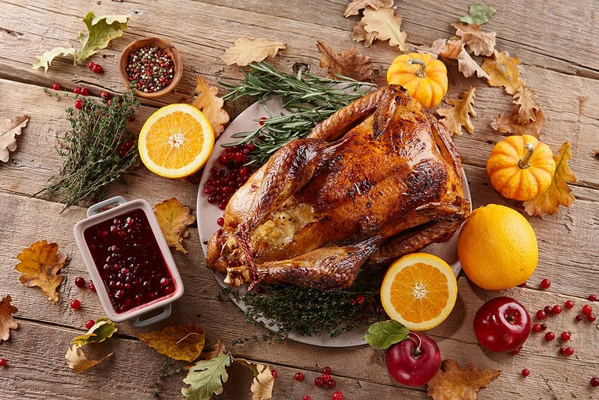 christmas turkey on a white plate surrounded by autumnal leaves, pumpkins sliced oranges apples and a small white tray of cranberry sauce