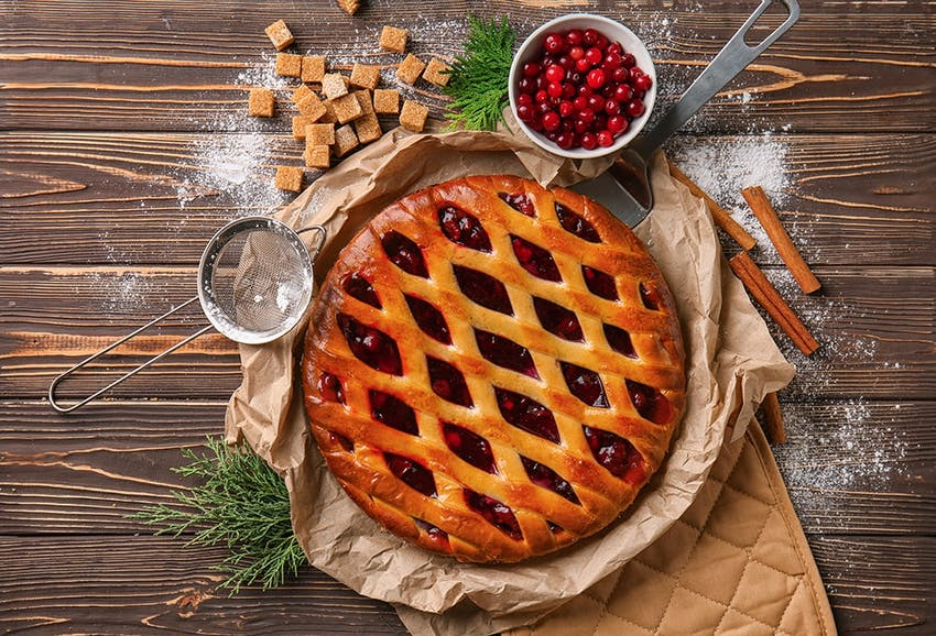 crispy golden christmas pie with a latticed top and a layer of cranberry sauce placed on a dish with brown baking paper on top of an oven glove
