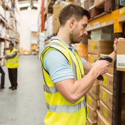 A man in a high vis searching the GTINs of products in a large warehouse