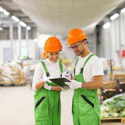 a man and women in white tops green dungarees and orange hard hats look at a clipboard in the middle of a food wholesaler warehouse