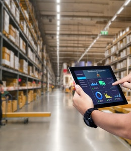 a man holds an iPad with a data report infront of stacked shelves inside a food wholesaler warehouse