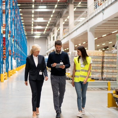 a woman in a suit and a woman in a green high vis walk through a food wholesaler warehouse with a man in a jumper holding an ipad