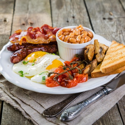 big english breakfast consisting of a pot of baked beans, brown bread, vine tomatoes, mushrooms, eggs, bacon and sausages