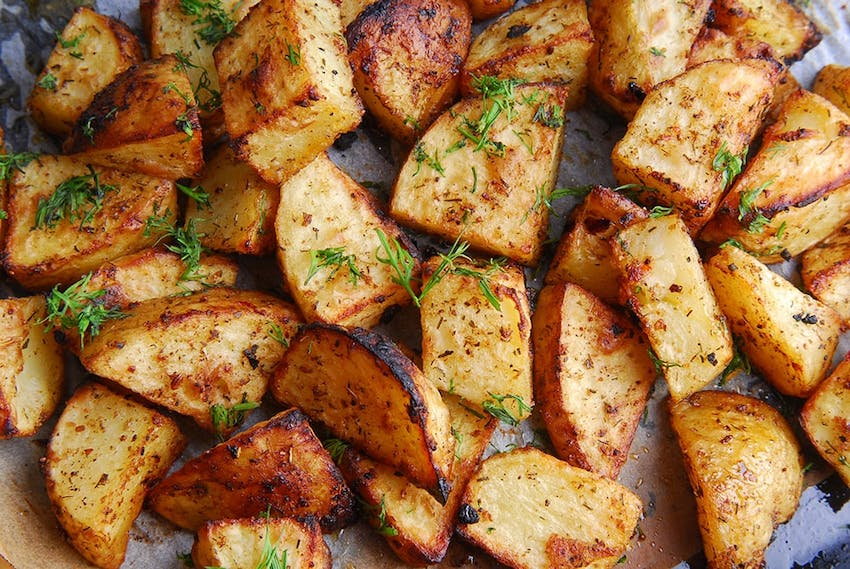 a baking tray of crispy roast potatoes topped with herbs