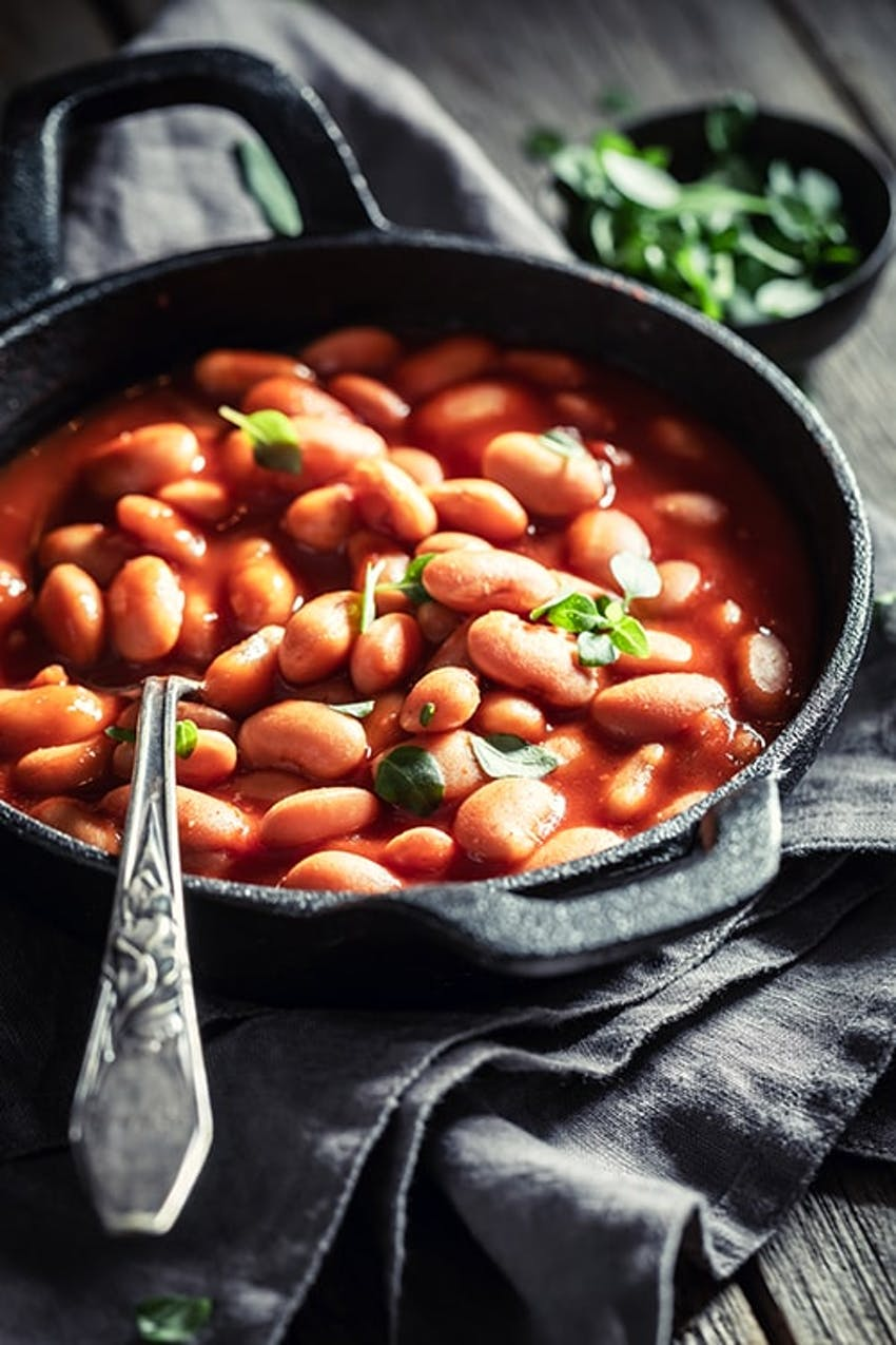 an iron skillet filled with baked beans topped with fresh herbs