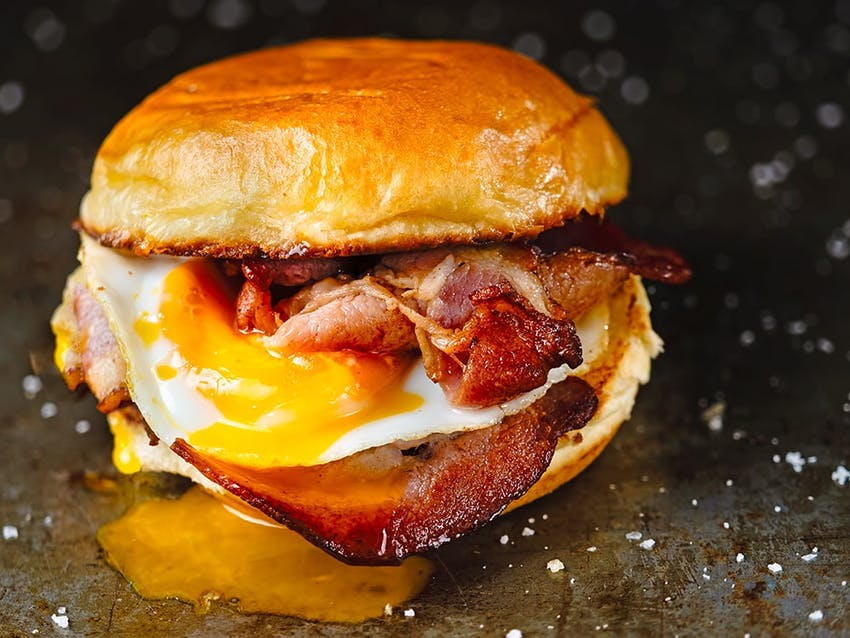 crispy bacon and a runny egg in a toasted golden bun with egg yolk oozing down the side of the bun