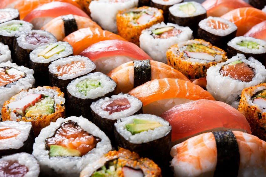 a dark brown circular bowl filled neatly with a range of different types of sushi, maki, sashimi, nigri on top of a dark marble table