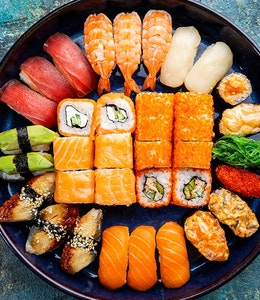 black dished filled with symmetrically placed colourful sushi