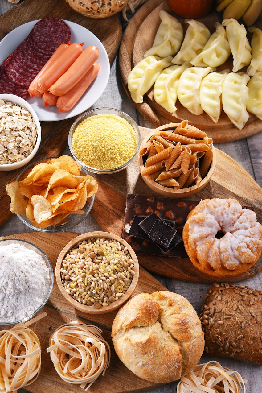 large food spread of gluten containing breads pasta grains crisps enchiladas sausages and spaghetti