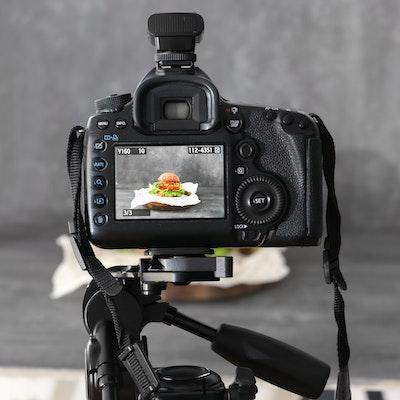 a dslr camera on a tripod shooting a burger on a grey backdrop