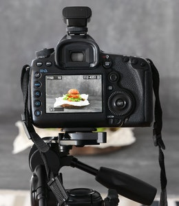 a dslr camera on a tripod shooting a burger on a grey backdrop