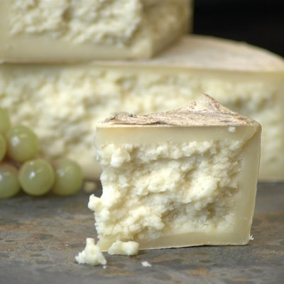 a triangular segment of creamy textured cheese in front of a bunch of green grapes and a cheese wheel