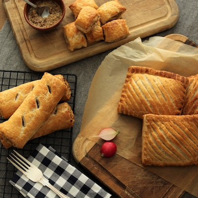 a range of fields and forest foods freshly baked sausage rolls, mini sausage rolls, and pasties on cooling racks and wooden chopping boards