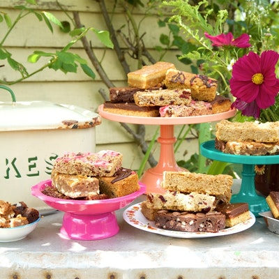 honeybuns gluten free cakes served on colourful tiered cake trays next to a cake tin on an outside garden table
