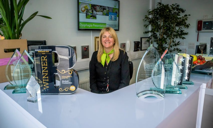 birchalls staff member sits behind the birchalls front desk surrounded by business awards and trophies