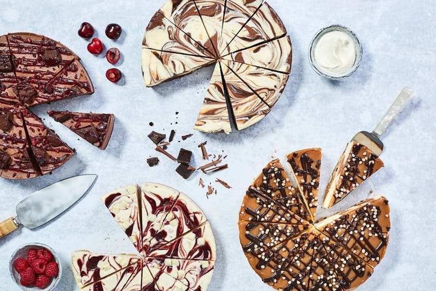 four varying flavours of cheesecakes all equally sliced into 12 slices on a marble tabletop with berries and cherries and chocolate