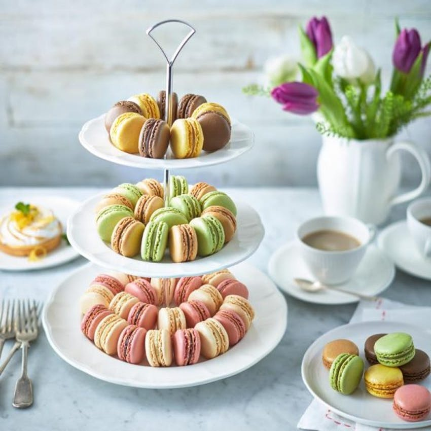 brioche pasquier mini lime,vanilla,chocolate,cream and strawberry macarons on a tiered cake tray next to a cup of tea and purple and white tulips