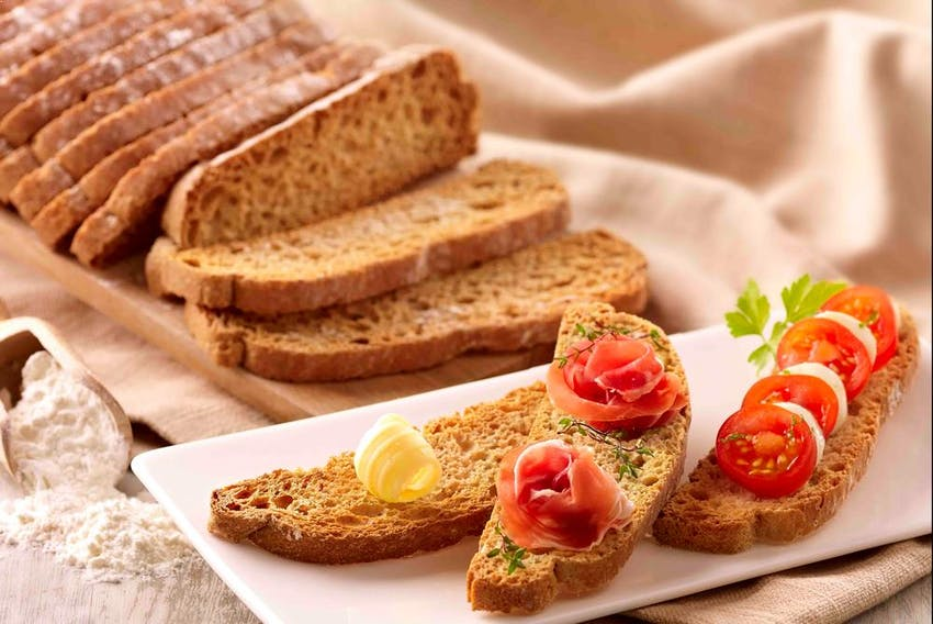 a sliced brown loaf of brioche pasquier bread with a swirl of butter, roses of parma ham and chopped vine tomatoes