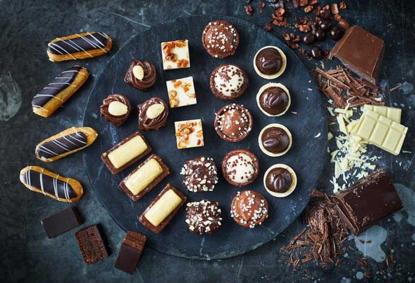 flatlay of brioche pasquier baked chocolate eclairs, brownie bits and chocolate treats on a dark marble surface