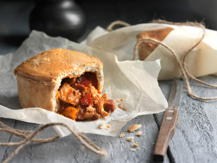 celtic pie co chicken and chorizo pie halved with filling pouring out onto baking paper on top of a grey wooden table