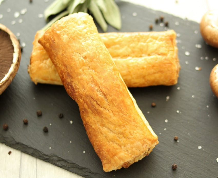 two fields and forest meat free sausage rolls balanced on one another next to a mushroom and scattered with peppercorns and salt
