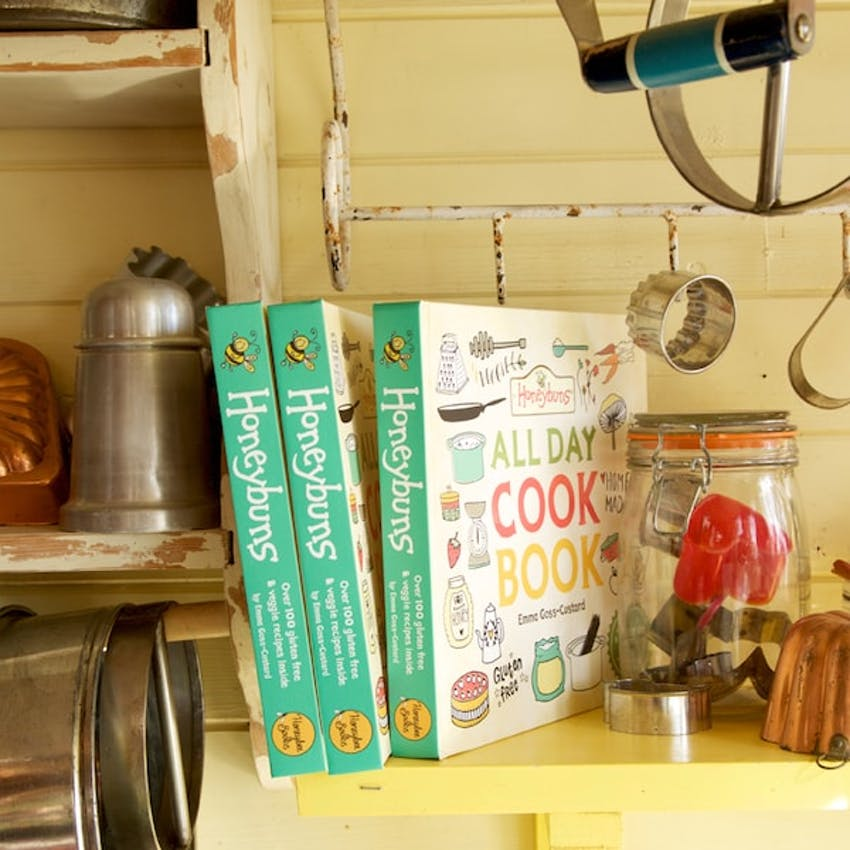 three honeybuns all day cookbook on yellow kitchen shelf surrounded by kitchen utensils and jars