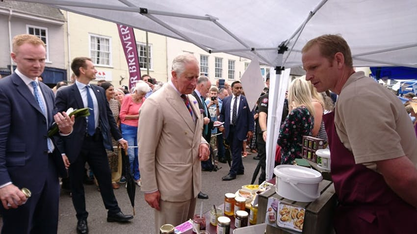 prince charles browsing the products on the otter vale farmers market stall with a crowd watching