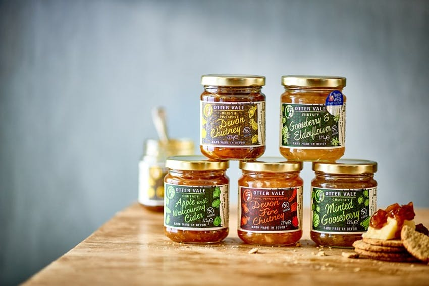 5 otter vale chutney flavours stacked in a pyramid style on a wooden table behind some crackers and cheese