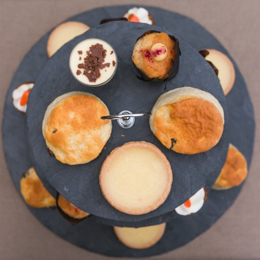 birds eye view of terrys patisserie afternoon tea box with tiered cake tray with various baked goods