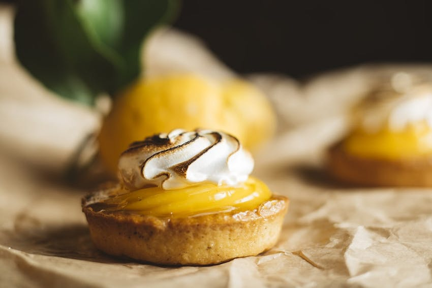 small lemon meringue tart with blow torched meringue and lemon curd on baking paper