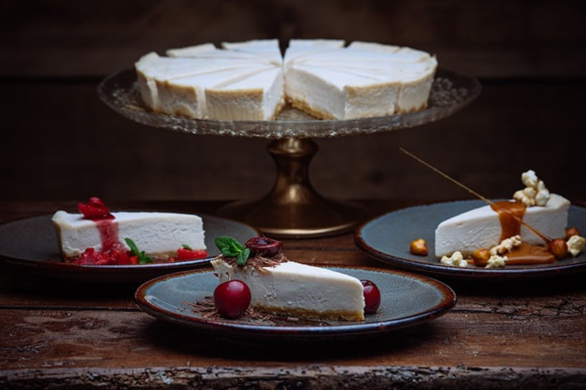 a whole central foods new york style cheesecake on a clear plated stand with three slices on grey plates topped with sauce berries and fresh mint