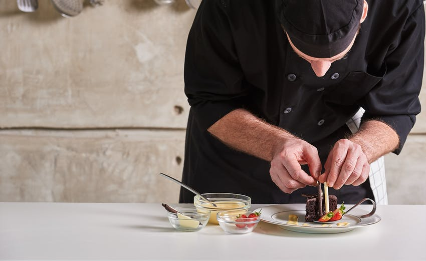 chef in black uniform carefully and cautiously decorates a dessert